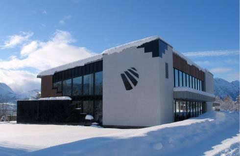 Trebygg med elementer i bygningssten i snølandskap